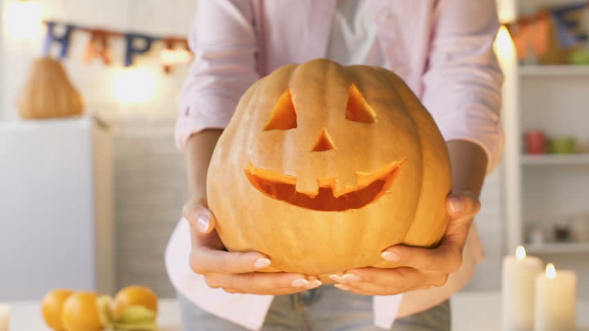 Female hands showing funny carved pumpkin into camera, handmade work, close-up | Shutterstock HD Video #1017734869
