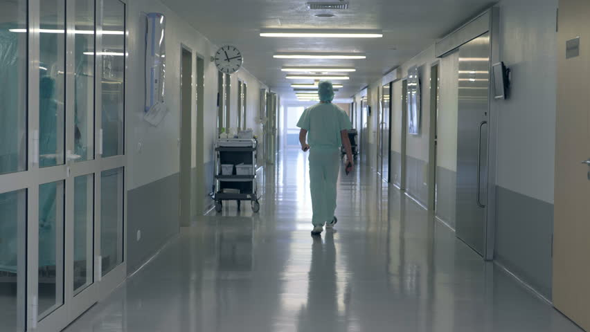 A man walking in a clinic hall. Person in doctor uniform walks in a hospital building.