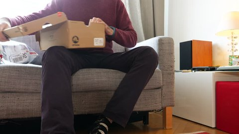 PARIS, FRANCE - CIRCA 2018: Young man unboxing new fashion running shoes from Crocs shoes from the delivery parcel