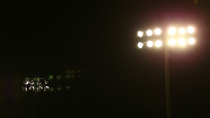 Stadium Lights at High School Football game on Friday Night.  Night Scene, dark with lights and lens flares from lights. | Shutterstock HD Video #1017799249