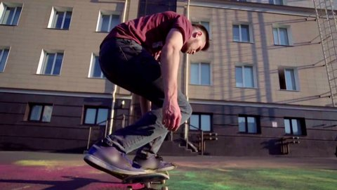 Skateboarder does extreme flip trick with colored powder in slow motion. paints fly in different directions. concept of fun and sports