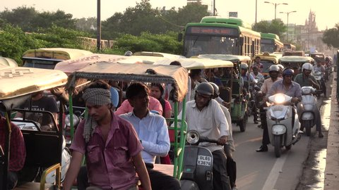 NEW DELHI, INDIA - SEP 8: Auto rickshaws, push bikes and pedestrians in heavy traffic scene on bridge on September 8, 2018 in New Delhi, India