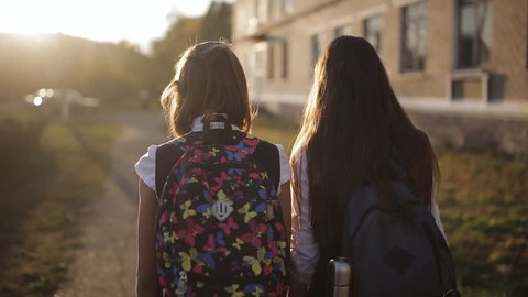 Girlfriend Schoolgirls with backpacks in sunset light coming home from school, the view from the back side.