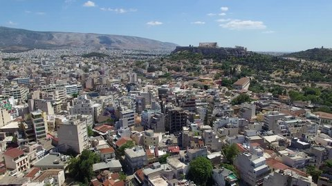 Aerial shot lowering into modern Athens neighborhood with acropolis on a hill at the horizon