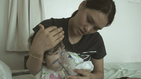 Little asian girl inhaling through inhaler mask with her mom at the hospital.