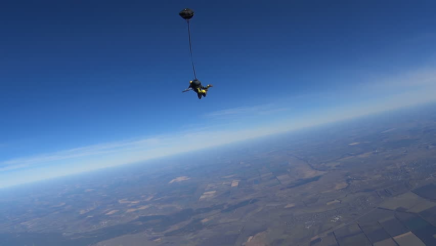 Parachutists Jumping in Tandem out of an Airplane. Skydiving. Tandem jump. Long free fall. Slow Motion. The instructor and man are enjoying the sky diving. Extreme video.