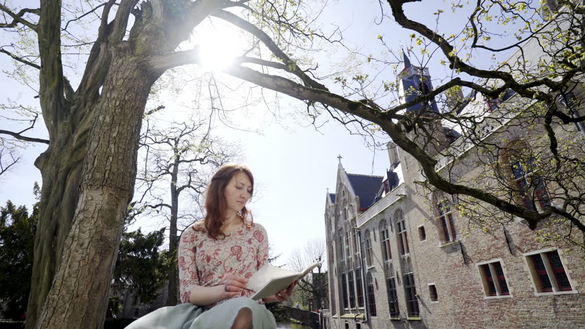 Motion panoram around woman sitting under tree. Young girl in sun shine turning page in paper note on knee at background medieval castle and narrow canal between buildings | Shutterstock HD Video #1017987529