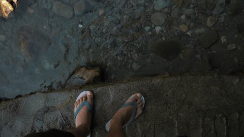 4K Indian boy steps into water and walks through the shallow stream wearing flip-flops