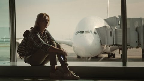 A single woman is sitting on the windowsill in the airport terminal amid a huge airliner. Loneliness and parting concept