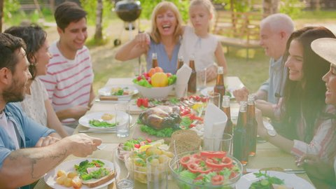 Big Family Garden Party Celebration, Gathered Together at the Table, Eating, Joking and Having Fun. Gliding Shot Over the Table.