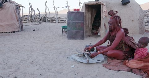 4K view of Himba woman in traditional dress with young child, putting a small pot on a fire outside their hut within their small compound, Namibia