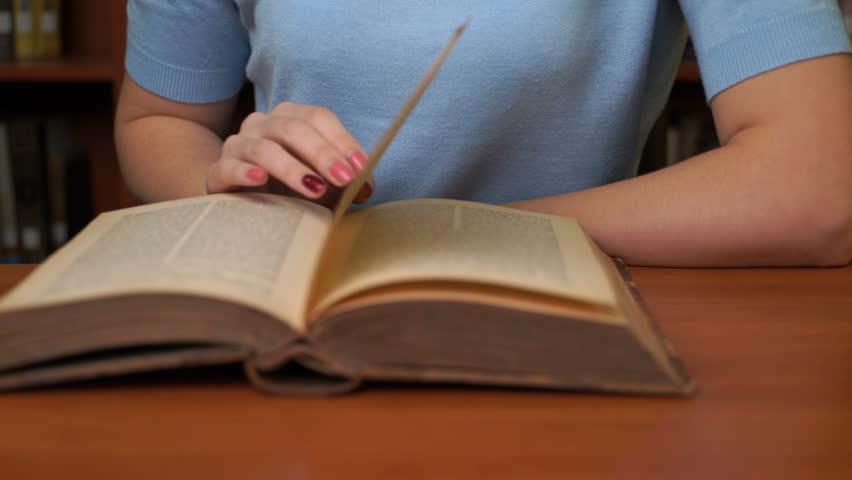 Footage pretty woman read book in library office. 4k education video | Shutterstock HD Video #1018037389