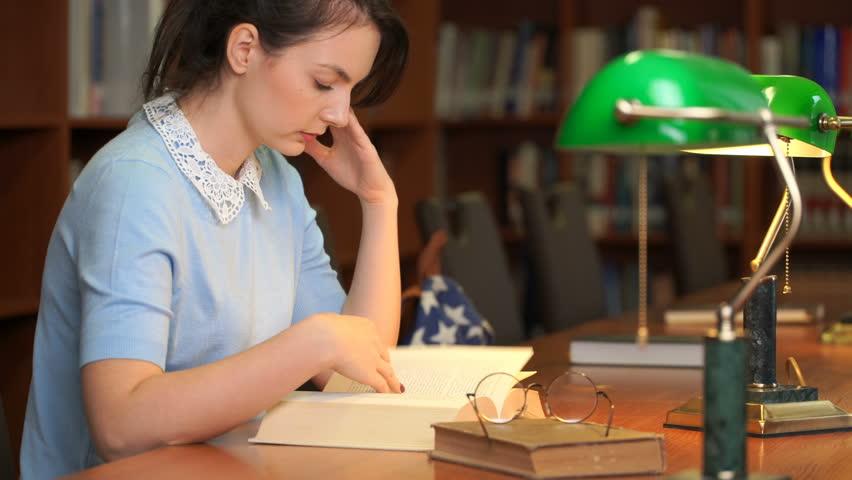 Footage portrait of schoolgirl doing their homework in library. Pretty woman read book in library office. 4k education video | Shutterstock HD Video #1018076419