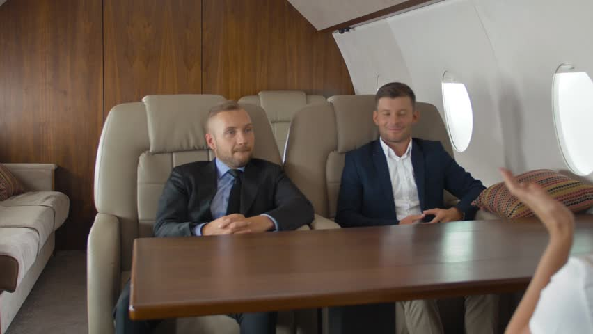 Premium view of businesspeople have meeting in corporate jet. Wide shot. Two confident male entrepreneurs and successful female businesswoman. Private jet first class location. Slow motion. | Shutterstock HD Video #1018124209