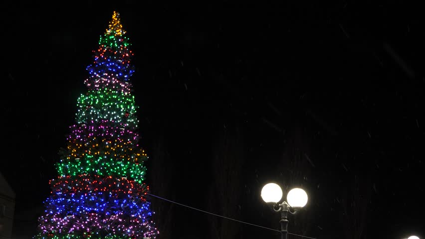In city park is shining Christmas tree decorated with garlands and colorful balloons against night sky. little snow falls | Shutterstock HD Video #1018157839