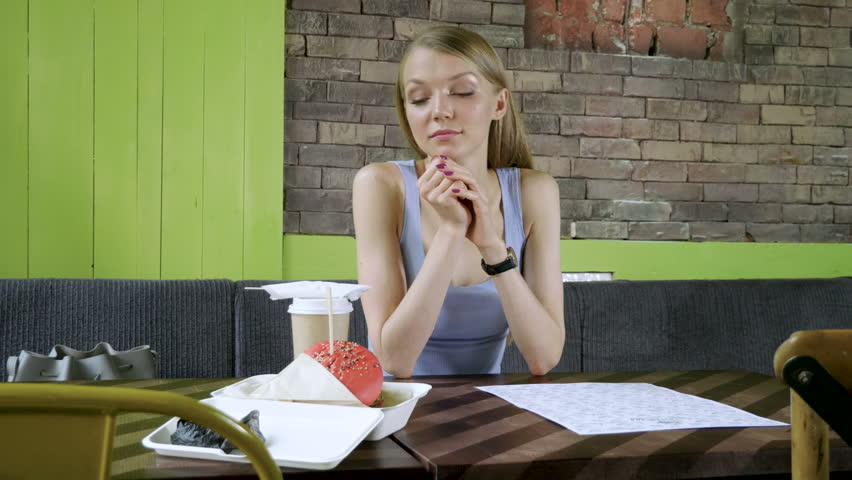 A young woman wearing black rubber gloves and going to eat a hamburger and drink coffee. 4K