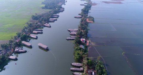 Drone footage of the Kolloam-Kottapuram waterway with its many houseboats parked or navigating it and the huge wetland of Kerala backwaters around near Alappuzha, Kerala, India.