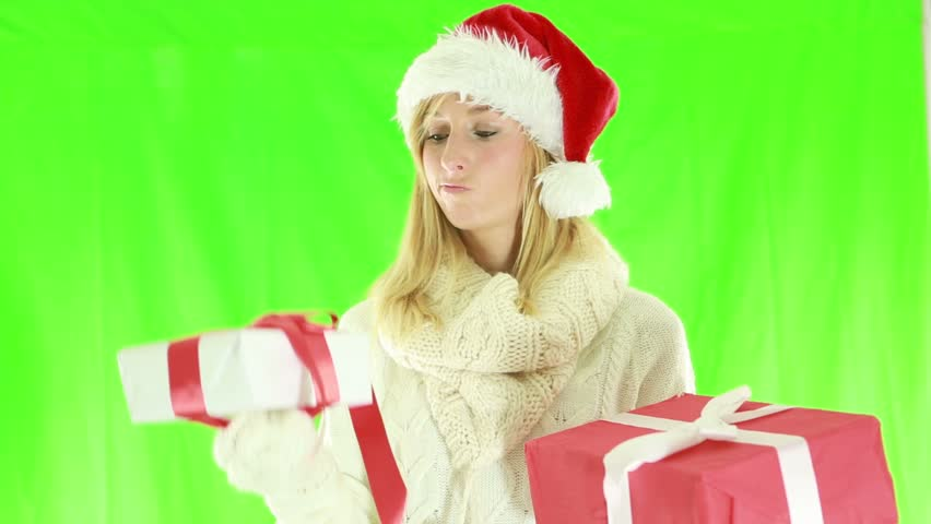 Woman choosing Christmas presents. Young woman trying to decide which Christmas present to buy. Green screen    Shutterstock HD Video #1018174819