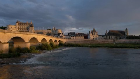 Amboise-France/Loire - October 10 2018 - The bridge and the Royale d'Amboise castle, along the Loire river at sunset - Motion view