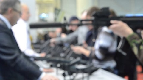 Abstract Defocused Blurred Background. Weapon optics sight of sniper rifle with man close-up. Several large-caliber weapons on table. Firearms gun submachine sniper rifle weapons close-up.