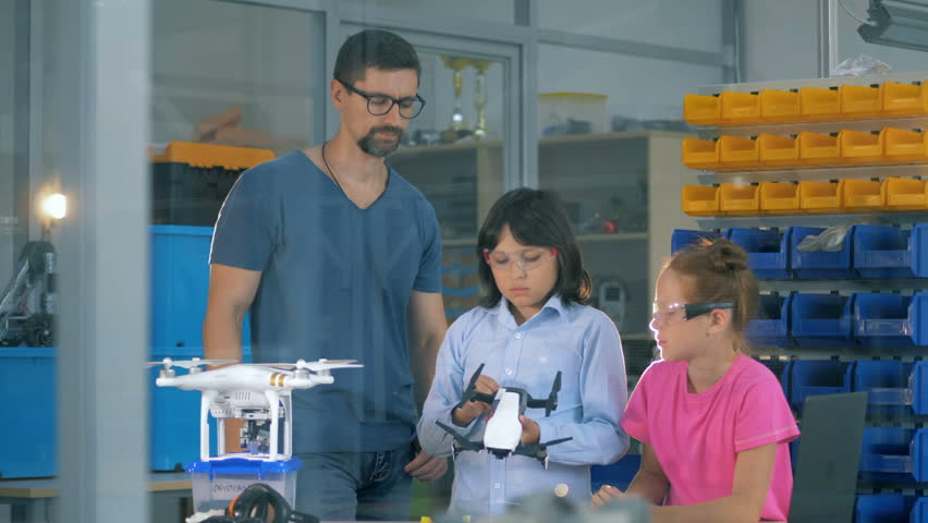 Engineer and two scgool children reassembling a quadcopter. Innovation in education concept. | Shutterstock HD Video #1018188379