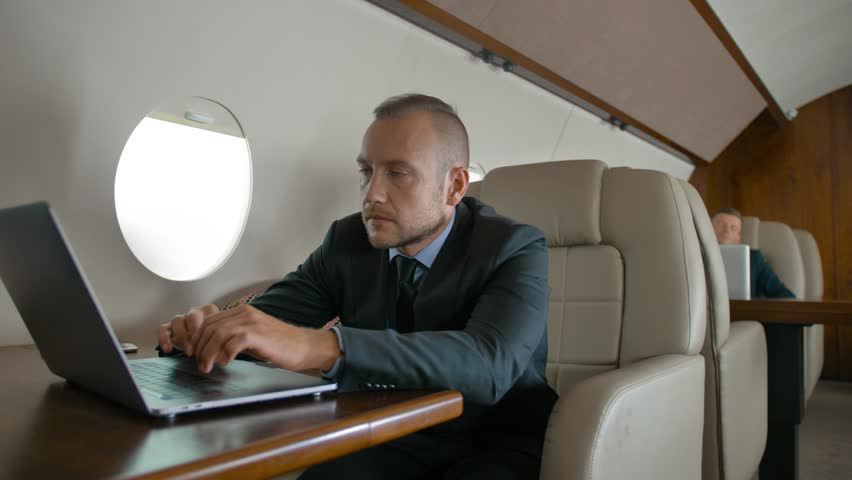 Entrepreneur traveling on his private jet. Confident and successful businessman working on modern thin laptop on expensive wooden table. Glidetrack movement. | Shutterstock HD Video #1018189819