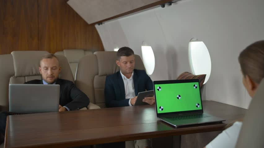 Businesspeople with laptops have meeting in corporate jet. Green screen ready for programm track replace laptop monitor. Three entrepreneurs discussing about business.   Shutterstock HD Video #1018189849