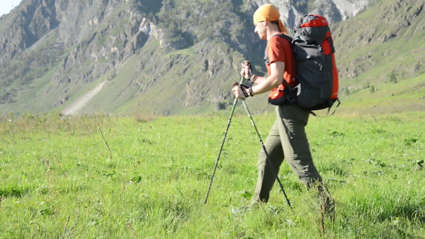 FHD Hiking man walking on green mountain meadow with backpack. Tourist travelling in sunny outdoors. Summer sport and recreation concept. | Shutterstock HD Video #1018195309
