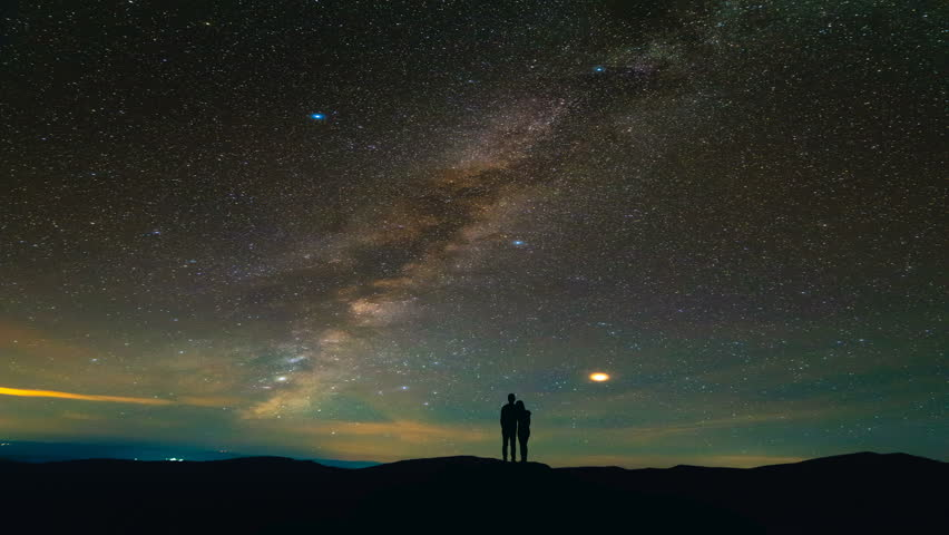 The couple standing on a background of a picturesque starry sky. time lapse #1018208599