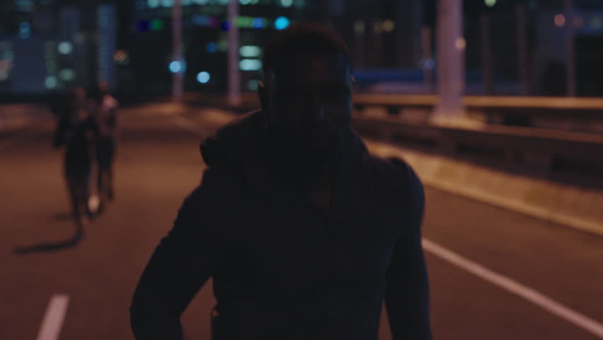 African american man athlete running in competition race intense endurance challenge urban city night | Shutterstock HD Video #1018213609
