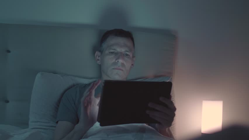 Man Speaking on the phone and looking at the tablet while in bed at night   Shutterstock HD Video #1018219579