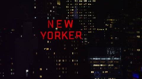 New York City, United States of America CIRCA - 2018. Aerial view of the New Yorker neon sign and skyscrapers, dark night lighting. Wide shot. 4k shot with a RED camera.