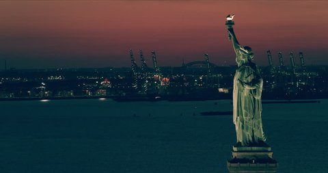 Aerial view of the Statue of Liberty, New York City, dark sunset light. Wide shot. 4k shot with a RED camera.