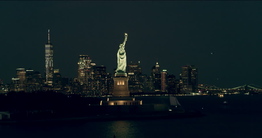 Aerial pan of the Statue of Liberty and Manhattan skyline, New York City, dark summer night light. Wide shot. 4k shot with a RED camera.