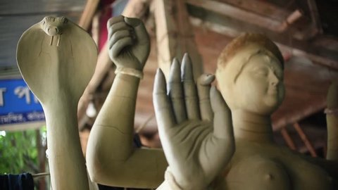 Unfinished clay sculptures of Hindu Gods and Goddesses are kept under a shade