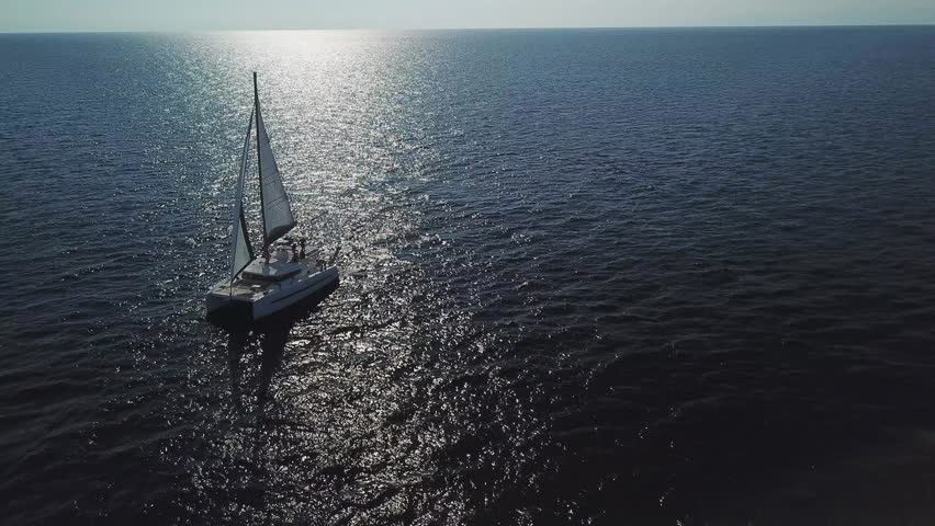 Aerial front side view of Catamaran sailboat sailing in full sail on a dark blue sea with reflexes in backlight | Shutterstock HD Video #1018352839