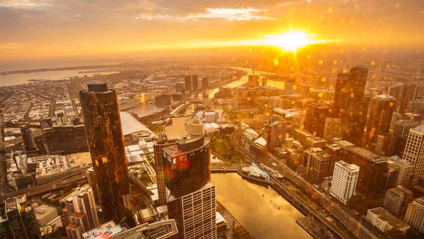 An aerial view of Melbourne cityscape including Yarra River and Victoria Harbour in the distance. Timelapse during sunset with beautiful sun ray bursting through fast moving clouds. Timelapse Zoom In.