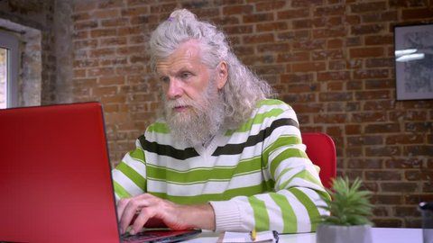 Cute ancient male is sitting at his workplace and looking at camera precisely, white long beard and hair, funny look, brick office illustration
