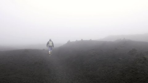 Man walking on Etna volcanic surface into fog and clouds on summit during hiking day in Sicily Italy