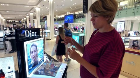 New York, USA - September 6, 2018: Woman trying parfume in Macys store