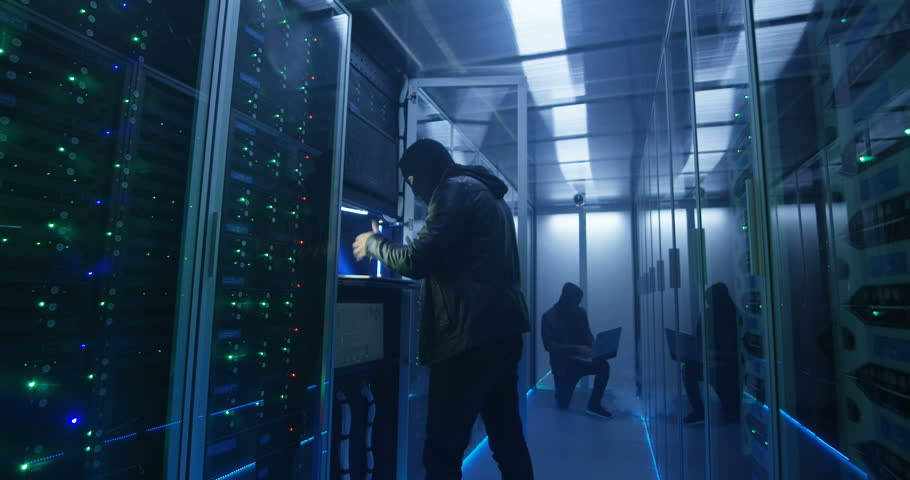 Wide, slow motion shot of a two hackers finishing hack and escaping a spark and smoke-filled corporate data center | Shutterstock HD Video #1018411279