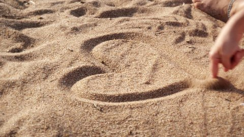 Drawing Heart Shape In Sand. Female hand drawing a heart shape on the sand of a beach