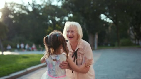 Charming granddaughter running down the street to beloved grandmother with blonde hair, hugging. Nice family relationships. Outdoors. Summertime. Flowerbed