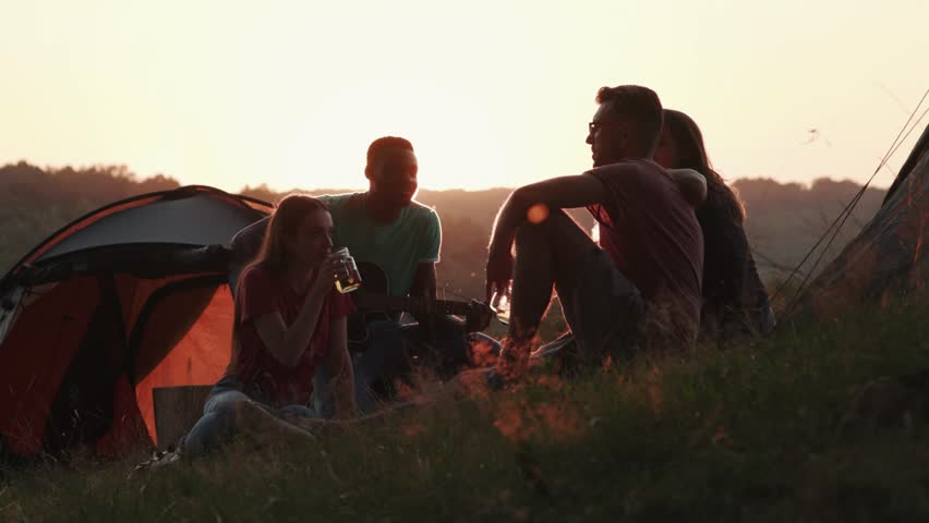 Silhouette of four friends on sunset light, actively communicating and listening to a man playing on guitar. Cheerful mood, having fun, relaxation. Tourism concept, coziness | Shutterstock HD Video #1018481509