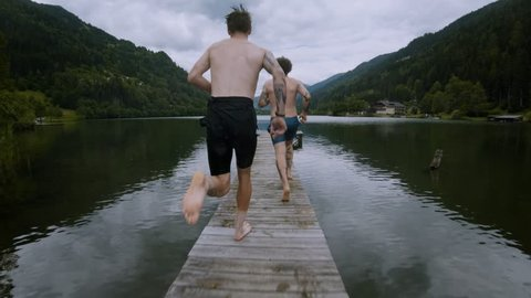 Two friends on summer vacation or holiday run on wooden boardwalk on alpine mountain lake, jump into cold fresh clean water to get refreshed in heat, natural outdoor lifestyle