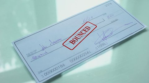 Cheque document bounced, hand stamps seal on official paper, insufficient funds
