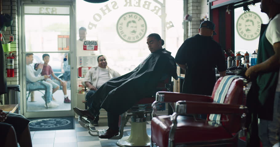 Happy cool male customers sitting in barber chair in interior hipster barbershop with soft day lighting. Wide shot on 4k RED camera on a gimbal.