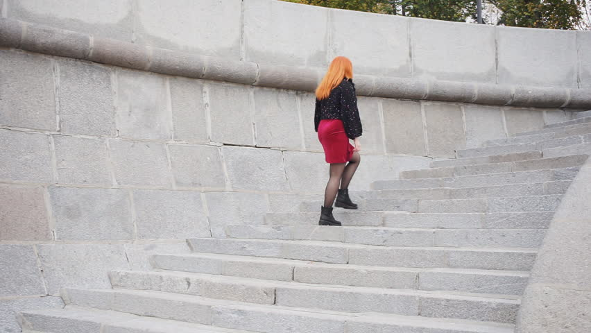 Girl climbs the stairs, turns around and looks into the camera #1018647769
