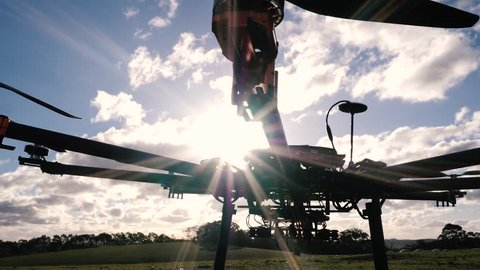 Siloutte of large octocopter drone in a paddock at sunset