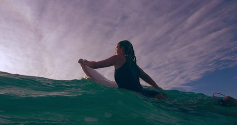 Young female surfer contemplating while lying on surfboard and swimming over an ocean wave in Australian beach with bright day lighting. Wide shot on 4k RED camera.